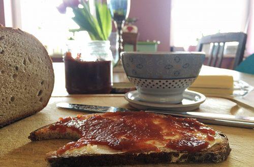Brot mit Apfelbutter, angeschnittener Brotlaib auf Brett, und Kaffeeschale