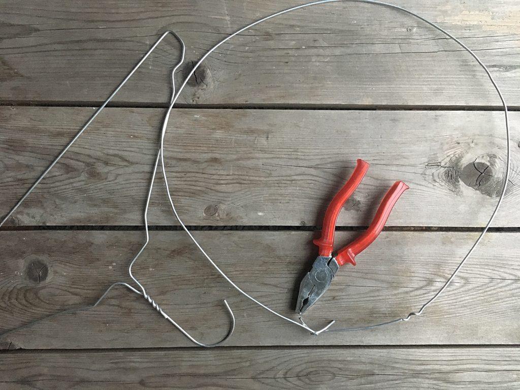 Drahtbügel, Dekoring und Zange auf Holzbrett