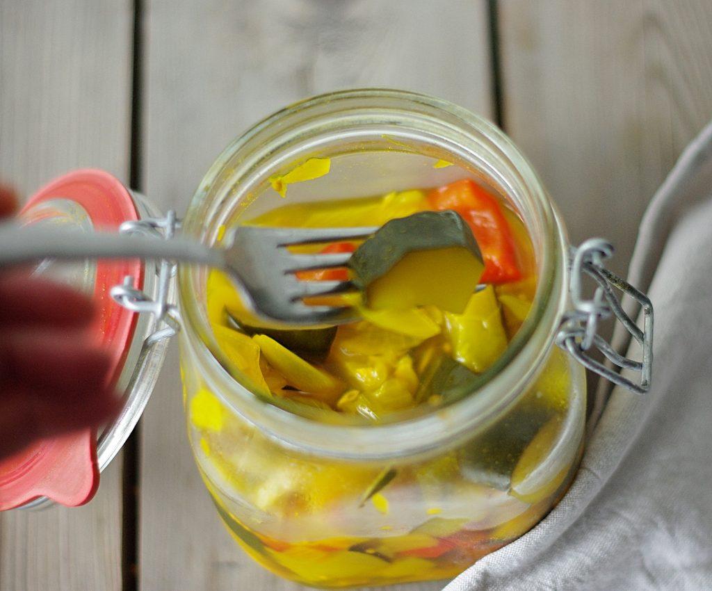 geöffnetes Bügelglas mit eingelegten Zucchini, Gabel mit Zucchini