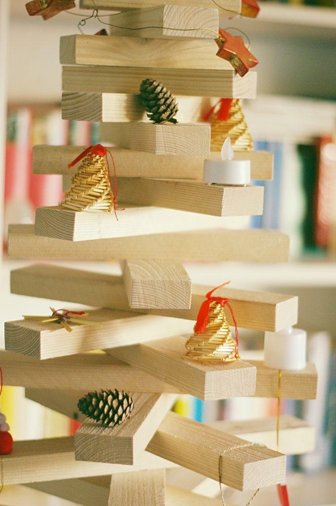 Teil eines Weihnachtsbaums aus Holz mit Tannenzapfen und Weihnachtsschmuck aus Bast
