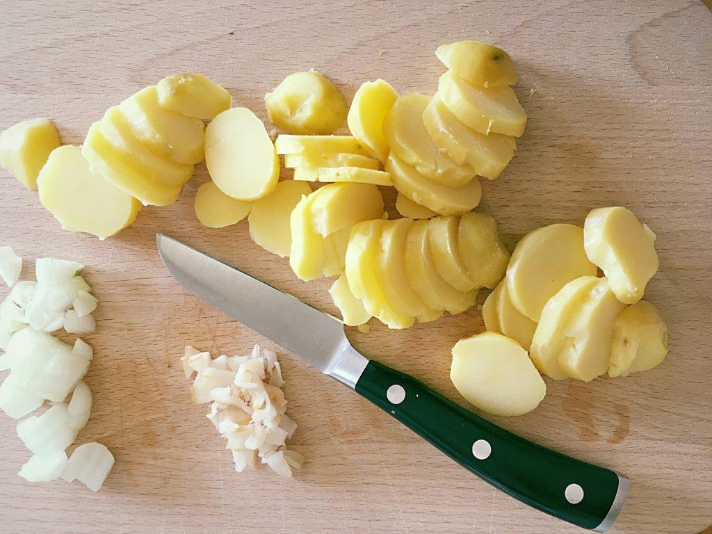 Holzbrett mit Messer, geschnittenen Pellkartoffeln, gewürfelten Zwiebeln und geschnittenem Speck