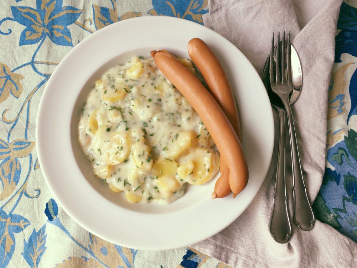 Teller mit Bechamelkartoffeln und Wiener Würstchen